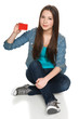 Young teen female sitting on floor showing blank credit card