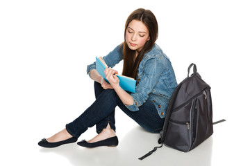 Young female sitting on floor with backpack reading a book