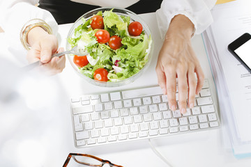 Young businesswoman eating a salad while working  in office.