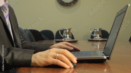 Businessman moving a computer mouse and typing on the Notebook