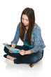 Young female sitting on floor reading a book