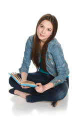 Young teen female student sitting on floor with a book