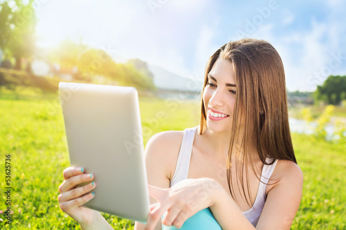 Happy young girl using tablet in the park