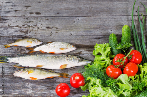 river fish with vegetables on wooden background