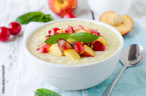 .Milk porridge with peaches and cherries