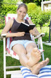 Junge freundliche Frau liest Buch im Gartenstuhl