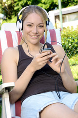 Junge Frau hört Musik im Garten