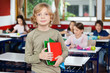 Schoolboy Holding Books While Standing In Classroom