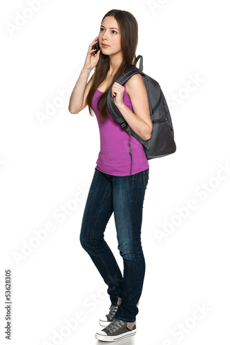 Full legnth of young female with backpack talking on cellphone