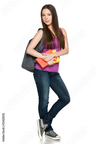 Smiling teen girl wearing backpack and holding books