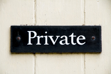 Old private sign screwed to a door