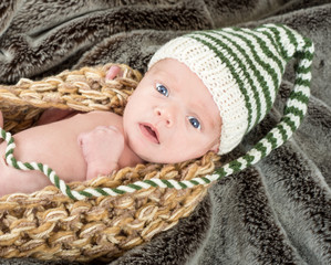 Adorable blue eyed newborn in a knit basket with a green and whi