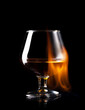 glass of wisky in fire flame on black background