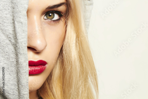beautiful blond woman in hood. red lips. text here
