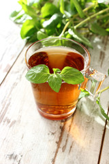 cup of tea with mint on wooden boards