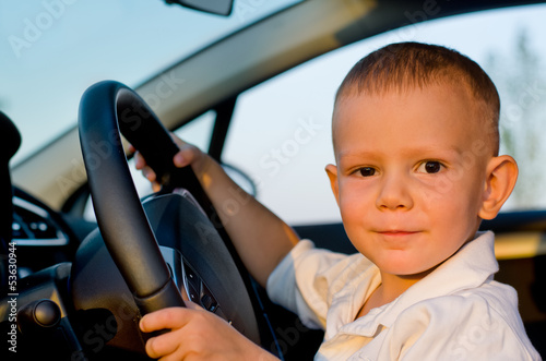 Little boy sitting behind the wheel of a car