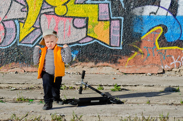 Cute little boy playing in front of graffiti