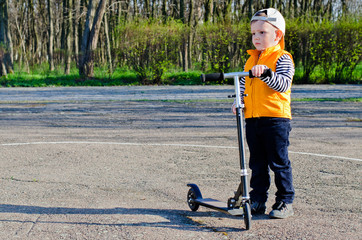 Handsome little boy holding his scooter