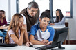 Happy Mature Teacher And Students Using Computer