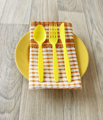 yellow spoon, fork, knife and napkin on yellow plate