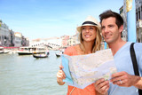 Cheerful tourists with city map in Venice