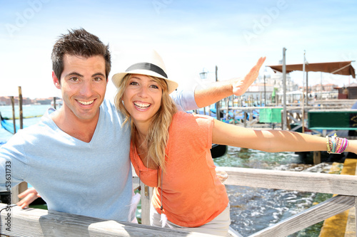 Cheerful couple stretching arms on a bridge in Venice