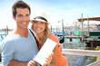 Cheerful couple in Venice showing tourist guide book