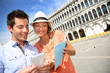 Couple in Venice looking at tourist information on smartphone