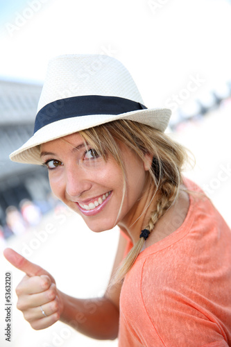 Smiling beautiful girl with hat showing thumb up