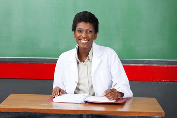Happy Female Teacher With Pen And Binder Sitting At Desk