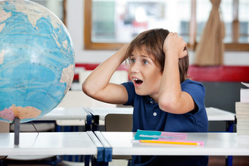 Shocked Schoolboy Looking At Globe In Classroom
