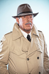Vintage detective man with moustache and hat. Wearing raincoat.