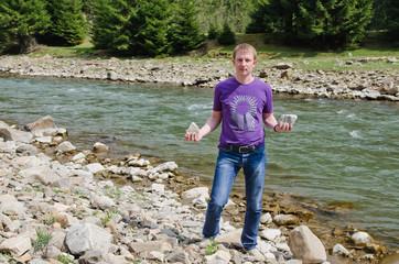 Man standing alongside a mountain river