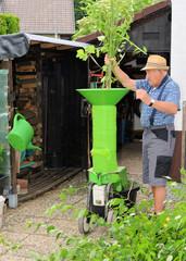 Mann mit Häcksler und Gartenschnitt