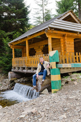 Man sitting at a wooden cabin on a waterfall