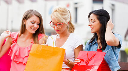 Girls Sitting on Bench With Shopping Bags