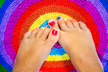 Female legs with a color pedicure
