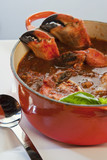 pot of crab cioppino with spoon, side view