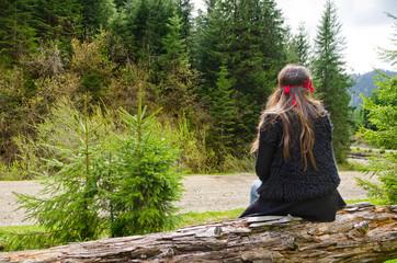 Woman waiting alongside a mountain road