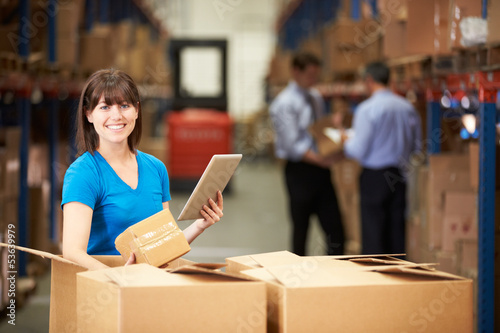 Leinwanddruck Bild Worker In Warehouse Checking Boxes Using Digital Tablet