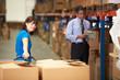 Female Worker Pulling Pallet In Warehouse