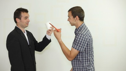 Two funny businessmen playing rock-paper-scissors