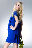 young blonde girl wearing blue cloth with bag posing