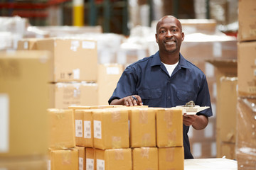 Worker In Warehouse Preparing Goods For Dispatch