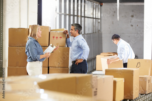 Workers Checking Goods On Belt In Distribution Warehouse