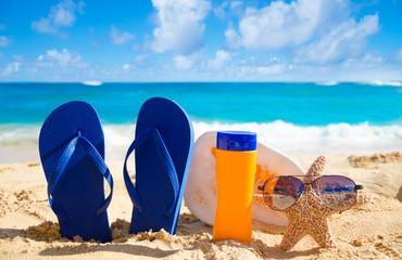 Flip flops, seashell, sunscreen and starfish with sunglasses on