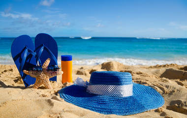 Flip flops, sunscreen, hat and starfish on sandy beach
