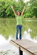 Glückliche lebensfrohe Frau am idyllischen Teich