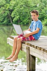 Freundlicher Jungendlicher sitzt mit Notebook am  Teich
