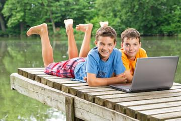 Zwei jugendliche Freunde mit Notebook am idyllischen Teich